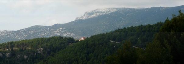 Au fond le Pic de Bertagne, point culminant des Bouches-du-Rhône (1041 m). Au milieu, la villa qui a remplacé le château des Espèces et qui jouxte le gouffre.